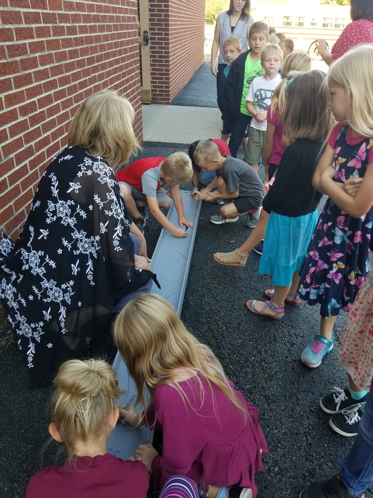 Students signing a beam that will go in the new school building.